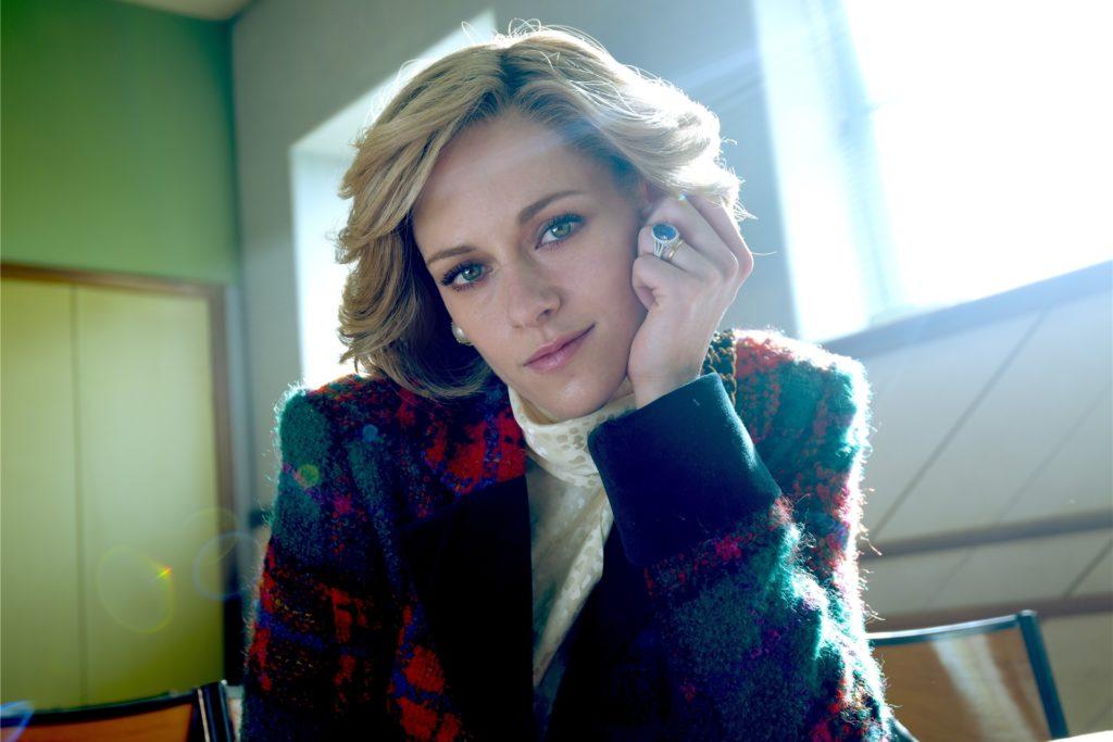 """Ein verträumter Blick, das Kinn auf die Hand gestützt, ein markanter blauer Verlobungsring am Finger: So präsentiert sich Kristen Stewart als Prinzessin Diana am Set zu """"Spencer""""."""
