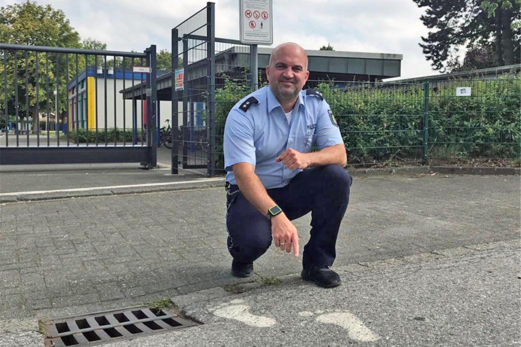 Polizist Jan Tonke zeigt auf die Fußabdrücke am Übergang. Deutliche Hinweise darauf, dass dieser nur für Fußgänger gedacht ist.