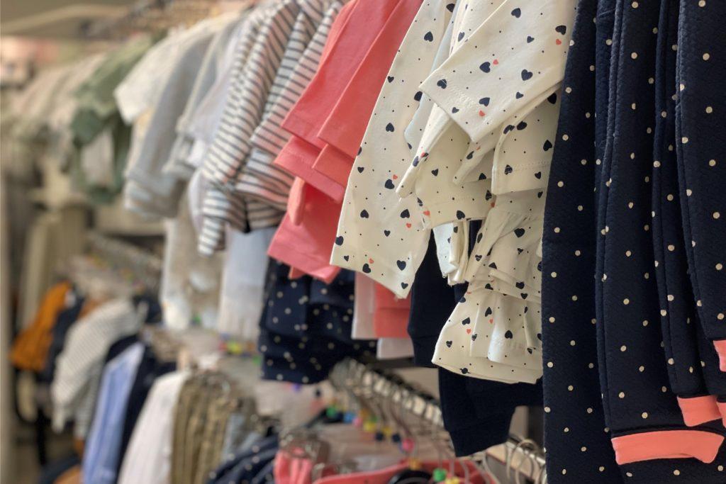 Kinderkleidung von Größe 44 bis Größe 122 wird an den Ständern hängen.