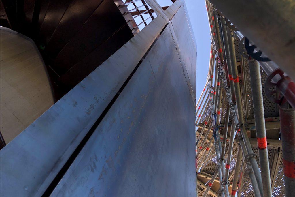 Hinter dem Gerüst ist bereits die künftige Außenansicht des Turms zu erkennen. Noch ist sie silbergrau, später wird sie rostbraun sein.