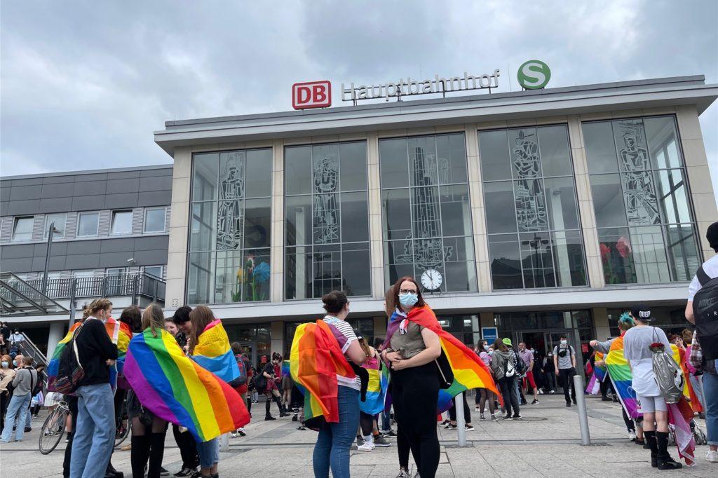 Vor dem Hauptbahnhof haben sich schon viele Menschen mit Flaggen versammelt.