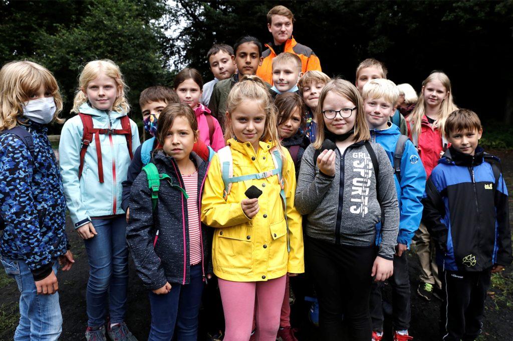 Alles über Holzkohle lernte die Klasse 4a der Heideschule an der ersten Station, dem Holzkohlemeiler, bei Ranger Mika Kowall.