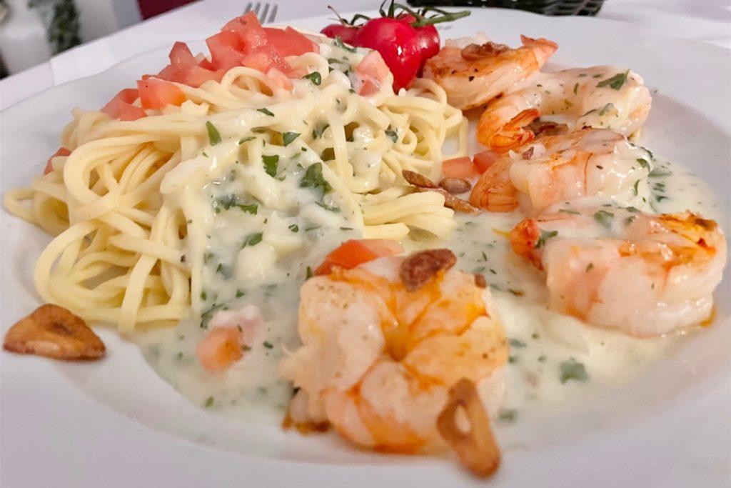 Scampi an Kräutersahnesauce mit einem Hauch Knoblauch und Tomatenstücken mit Fettuccine und Salat.
