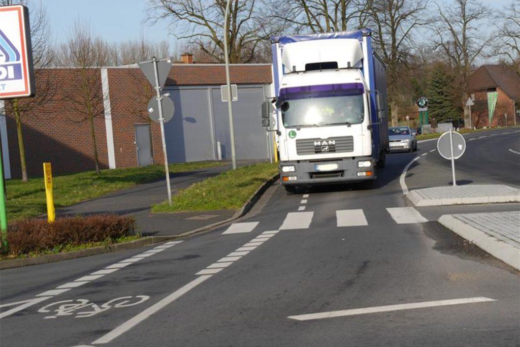 Hier geht es nur über den Schutzstreifen. Dieser darf von Lastern und Autos eigentlich nur überfahren werden, wenn sie dem Gegenverkehr ausweichen.