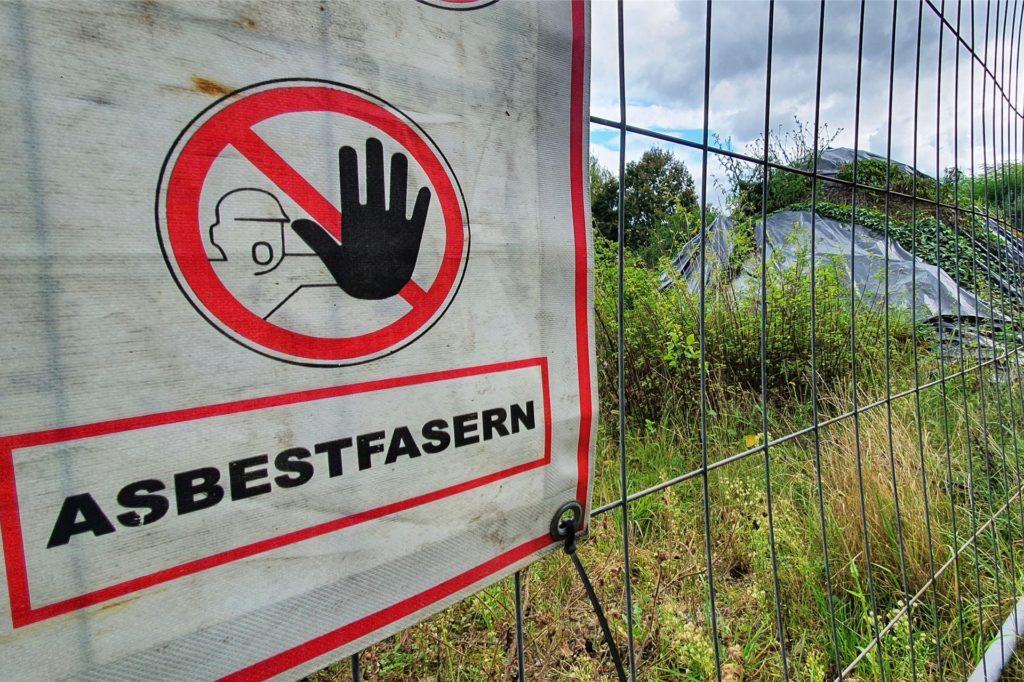 Ein Schild am Bauzaun warnt vor der Gefahr, die im Haufen lagert.